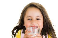 Cute little preschooler girl drinking a glass of Stock Image