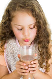 Cute little preschooler girl holding a glass of Stock Images
