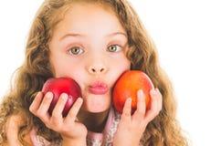 Cute little preschooler girl holding two peaches Stock Photography