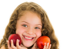 Cute little preschooler girl holding two peaches Royalty Free Stock Photos