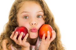 Cute little preschooler girl holding two peaches Royalty Free Stock Image