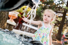 Cute little preschooler girl playing with a city fountain Stock Photography