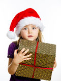 Cute little preschooler girl in red santa hat with gift box Stock Photos