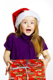 Cute little preschooler girl in red santa hat with gift box Royalty Free Stock Image