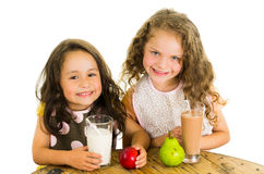 Cute little preschooler girls drinking milk and Royalty Free Stock Images
