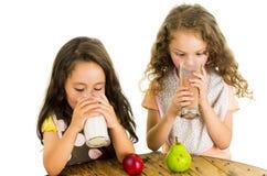 Cute little preschooler girls drinking milk and Royalty Free Stock Image