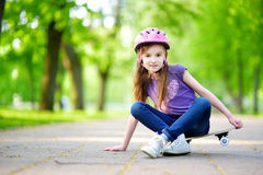 Cute little preteen girl wearing helmet sitting on a skateboard Royalty Free Stock Photography