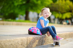 Cute little preteen girl wearing helmet sitting on a skateboard Stock Photos