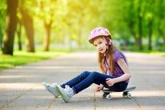 Cute little preteen girl wearing helmet sitting on a skateboard Royalty Free Stock Photo
