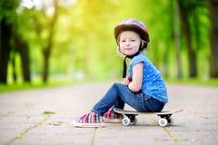 Cute little preteen girl wearing helmet sitting on a skateboard Stock Images
