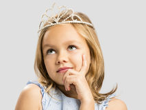 Cute little princess dreaming. Portrait of a cute happy little girl wearing a princess crown royalty free stock image