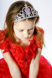 Cute little princess dressed in red  with crown on her head posi Royalty Free Stock Photo