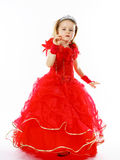 Cute little princess dressed in red  with crown on her head posi Stock Photos