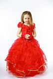 Cute little princess dressed in red dancing. Isolated on white b Stock Photo
