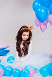 Cute little princess girl sitting among balloons in room over white background. Looking at camera. Childhood. Stock Photo