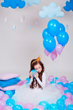 Cute little princess girl sitting among balloons in room over white background. Looking at camera. Childhood. Stock Image