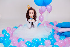 Cute little princess girl sitting among balloons in room over white background. Looking at camera. Childhood. Royalty Free Stock Images