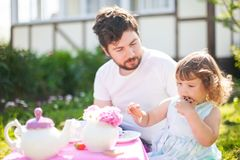 Cute little princess playing tea party with her loving father. Single father and his adorable toddler girl outdoors, playing tea party. Father watering his Stock Images