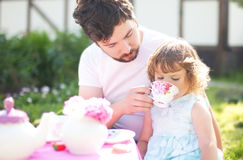 Cute little princess playing tea party with her loving father Royalty Free Stock Images