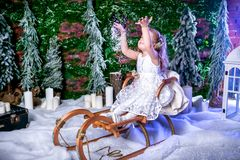 Cute little princess in a white dress sits on a sled and throws snow up stock image