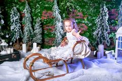 Cute little princess in a white dress is sitting on a sled and throwing snow stock photo