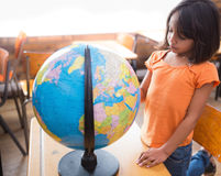 Cute little pupil looking at globe in classroom Stock Image