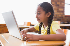 Cute little pupil looking at laptop in classroom Royalty Free Stock Photos