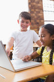 Cute little pupils looking at laptop in classroom Royalty Free Stock Images