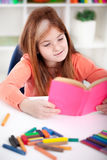 Cute little red-haired girl reading a book Royalty Free Stock Photography