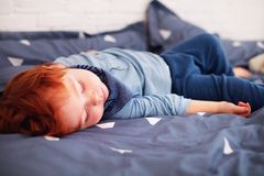Cute little redhead baby fallingasleep in parent`s bed Stock Photo