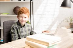 Cute little redhead boy smiling at camera while sitting at table with books. And laptop royalty free stock photo