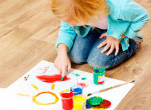 Cute little redhead girl painting. Stock Photos