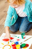 Cute little redhead girl painting. Royalty Free Stock Photo