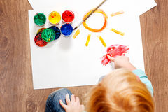 Cute little redhead girl painting. Royalty Free Stock Image