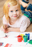 Cute little redhead girl painting. Stock Images