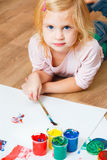 Cute little redhead girl painting. Royalty Free Stock Images