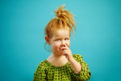 Cute little redhead girl picks her nose with finger on blue isolated. Children`s bad habit and how to get rid of it Royalty Free Stock Image