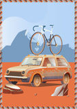 Cute little retro car with  bicycle on top goes by wonderful countryside road at sunset Royalty Free Stock Photos