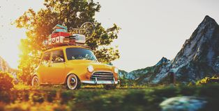 Cute little retro car goes by wonderful countryside road at sunset. Cute little retro car with suitcases and bicycle on top goes by wonderful countryside road at royalty free stock photos