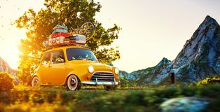Cute little retro car goes by wonderful countryside road at sunset. Cute little retro car with suitcases and bicycle on top goes by wonderful countryside road at stock photo