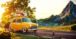Cute little retro car goes by wonderful countryside road at sunset. Cute little retro car with suitcases and bicycle on top goes by wonderful countryside road at stock image