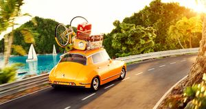 Cute little retro car with suitcases and bicycle on top goes by the road royalty free stock image