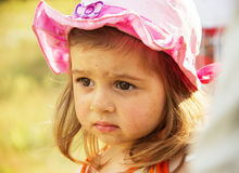 Cute little sad girl thinking in the park. At summer day Royalty Free Stock Image