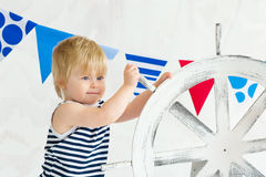 Cute little sailor twisting the wheel. Adorable little boy dressed as a mariner in a striped vest and holding wooden steer wheel Royalty Free Stock Photography