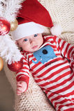 Cute little Santa baby posing beside Christmas tree at cozy home with New Year decoration Stock Photo