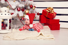 Cute little Santa baby posing beside Christmas tree at cozy home with New Year decoration Royalty Free Stock Images