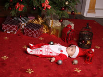 Cute little Santa baby sleeping beside Christmas tree with a lot of presents Stock Image