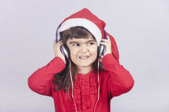 Cute little Santa girl listening to music Stock Image