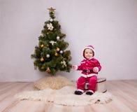 Cute little Santa posing at studio near New Year tree Stock Photography