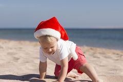 Cute little Santa in red hat on the sea beach. Royalty Free Stock Image